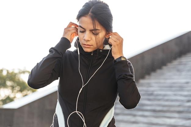 이어폰으로 음악을 듣고, 야외에서 운동하는 운동복을 입고 매력적인 젊은 피트 니스 여자의 닫습니다