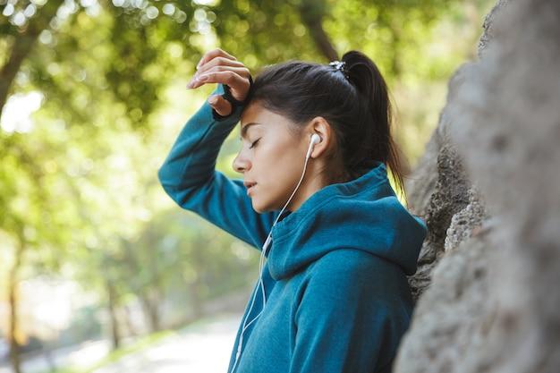 屋外で運動し、トレーニング後に休んでいるスポーツウェアを着ている魅力的な若いフィットネス女性のクローズアップ