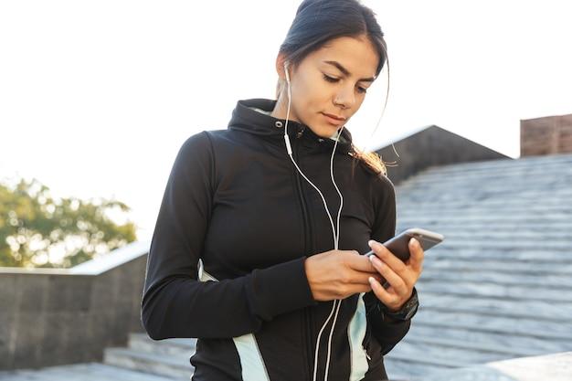 휴대 전화를 사용하여 야외에서 운동하는 운동복을 입고 매력적인 젊은 피트 니스 여자의 닫습니다
