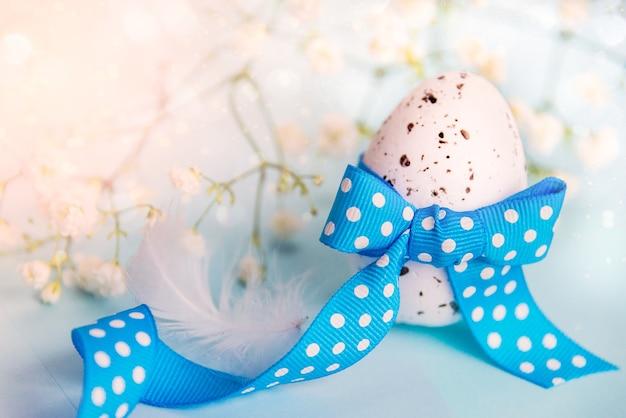Закройте пасхальное яйцо. весенние цветы и перо