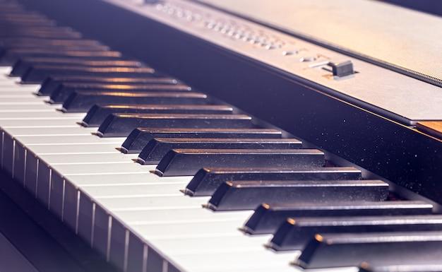 美しい照明の電子ピアノキーボードのクローズアップ。