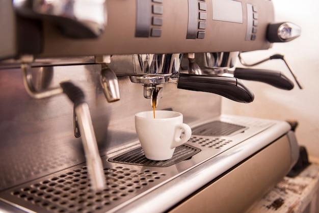 一杯のコーヒーを作るエスプレッソマシンのクローズアップ。