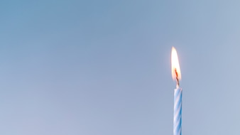 Close-up of an illuminated candle against blue background