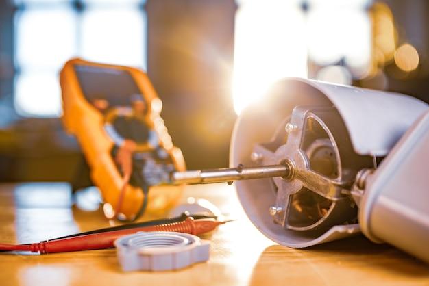Крупным планом - железный мотор от вентилятора домашнего охлаждения и тестовые инструменты, лежащие на столе во время ремонта в специализированной мастерской. концепция ремонта и восстановления поврежденного оборудования