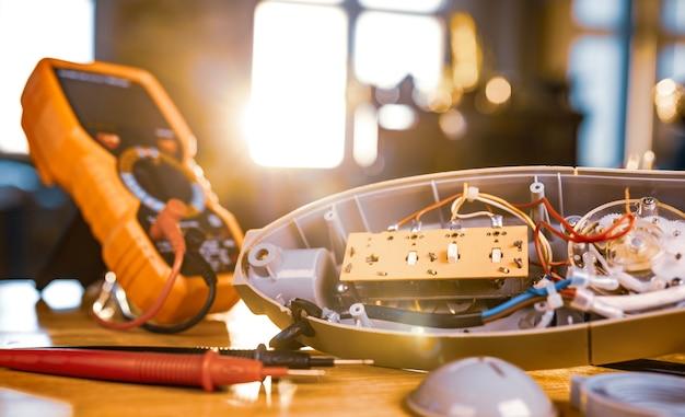 家庭用冷却ファンとテストツールからの鉄モーターのクローズアップは、専門のワークショップでの修理中にテーブルの上にあります。損傷した機器の修理と修復の概念