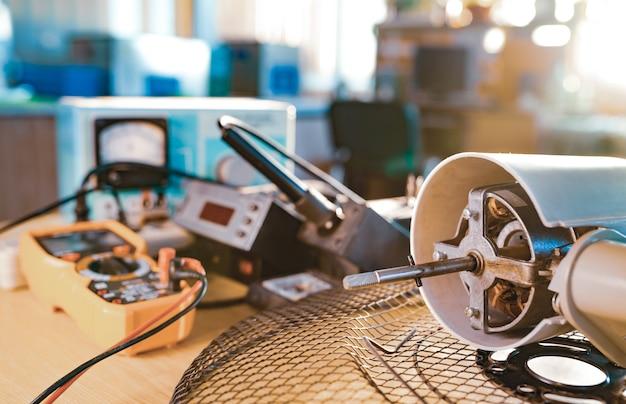 家庭用冷却ファンとテストツールからの鉄モーターのクローズアップは、ワークショップのテーブルの上にあります。損傷した機器の修理と修復の概念