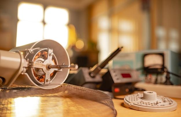 家庭用冷却ファンとtestindツールからの鉄モーターのクローズアップは、ワークショップのテーブルの上にあります。損傷した機器の修理と修復の概念