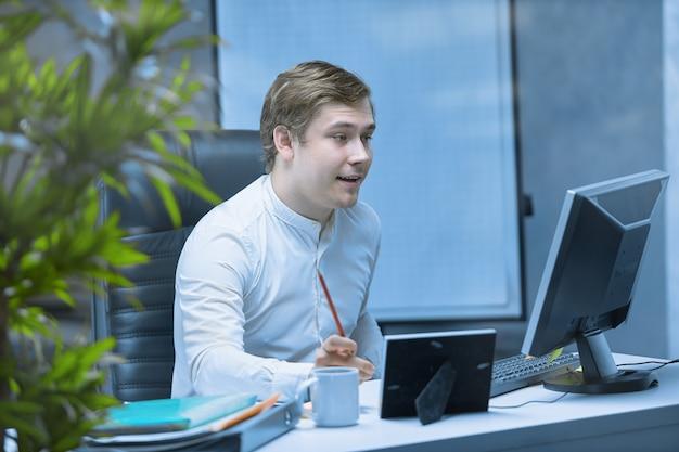 Крупный план офисного работника, сидящего за столом, сосредоточенного на работе