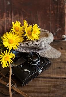 ヴィンテージの帽子と木製の背景に黄色い花の花束と古いカメラのクローズアップ。