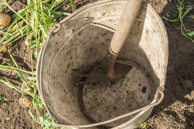 庭の土や草の背景に熊手と古い汚れたさびた鉄のバケツのクローズアップ。