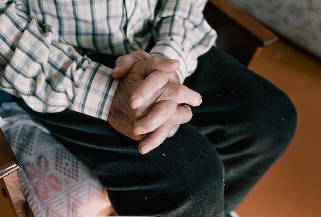しわやシミのある老人の手のクローズアップ。高齢者