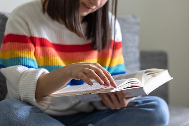 明るい色のセーターを着た少女が手に開いた本のクローズアップ。