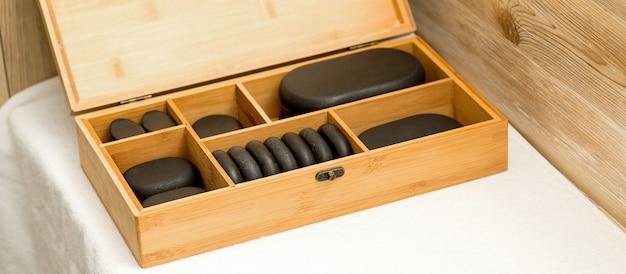 スパの黒い石で開いた木製のケースのクローズアップ