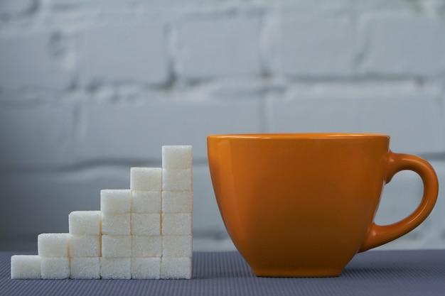 Конец-вверх оранжевой чашки и кубов белого сахара аранжировал в увеличивая столбцах на белой предпосылке, селективном фокусе