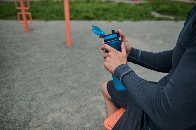 運動、ボディービル、屋外トレーニングの後に体に水分を補給する淡水ボトルを持っている認識できないアスリートのクローズアップ。トリミングされた画像