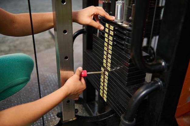 ブロックジム設備に体重を設定している認識できないアスリートのクローズアップ