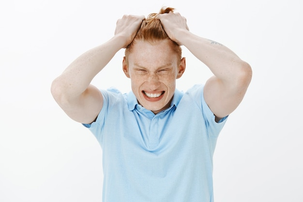 Крупным планом злой рыжий мужчина рвет волосы на голове и выглядит расстроенным, чувствуя себя под давлением