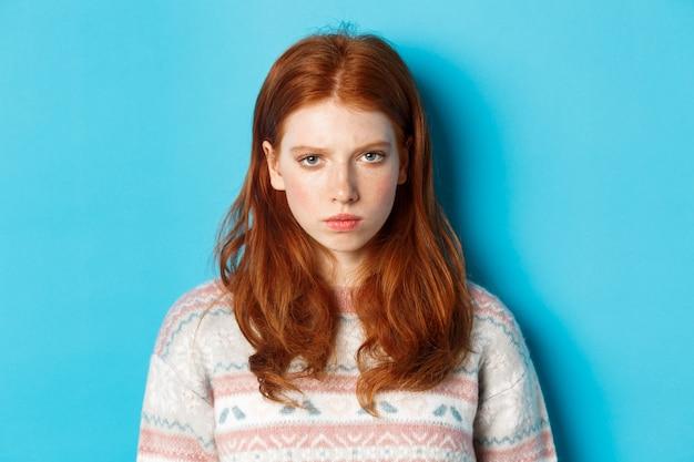 Крупный план разгневанной рыжей девочки-подростка, рассерженной в камеру, хмурящейся и надутой безумной, стоящей на синем фоне.