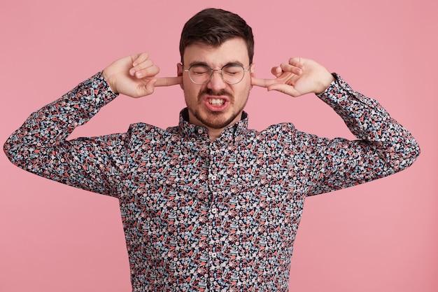 カラフルなシャツを着た怒っている若いひげを生やした男のクローズアップ、目を閉じたまま、2本の指で耳を閉じ、難聴のジェスチャーを示し、誰かを無視し、ピンクの壁を越えて