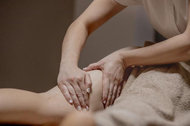ウェルネスセンターで若い女性のための抗セルライトマッサージのクローズアップ