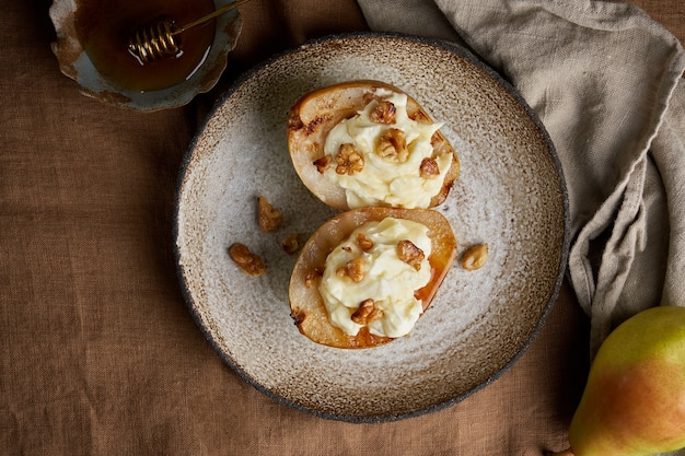 Закройте аппетитные сладкие груши на гриле с грецкими орехами и медовым осенним деревенским десертом