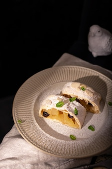 皿にシナモンとミントとリンゴのオーストリアのシュトルーデルのクローズアップ