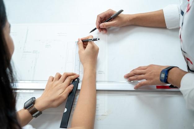 ブループリント計画コンセプトに取り組んでいる建築プロジェクト設計に描いた建築家のクローズアップ。
