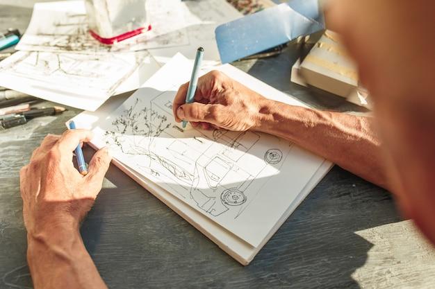 彼の飛行機のプロジェクトで建設プロジェクトをスケッチする建築家のクローズアップ