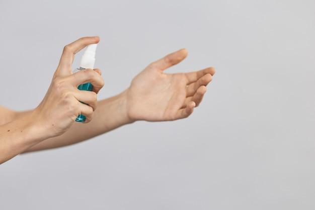 회색에 고립 된 소독 스프레이를 사용하는 팔 클로즈업, covid-19 동안 팔을 깨끗하게 유지하고 손을 청소하여 생명을 구하십시오