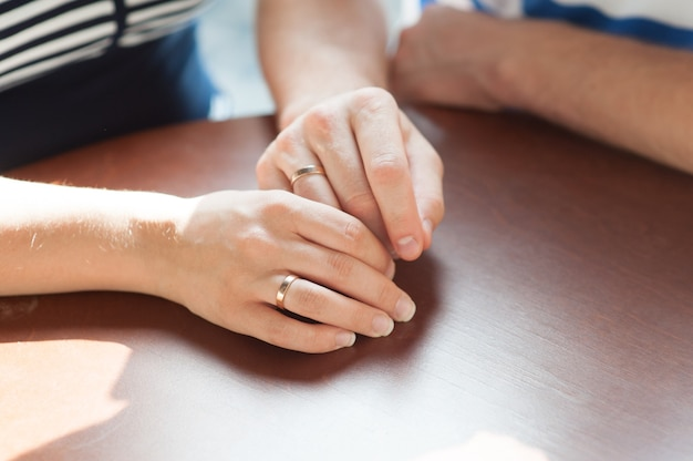 Закройте руки влюбленная пара, сидящая за столом в кафе.