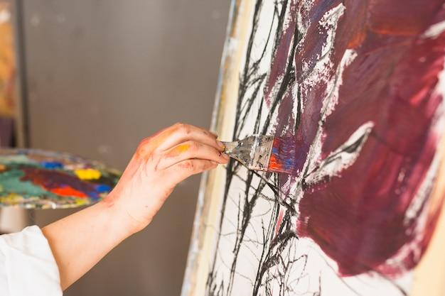 絵筆で芸術家の手の絵画のクローズアップ