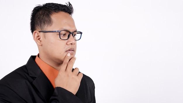 白い背景で考えるアジアのビジネスマンのクローズアップ