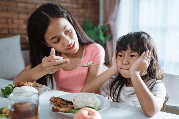 彼女の姉が彼女の食べ物を与えるとき、アジアの小さな女の子のクローズアップは食べることを拒否します