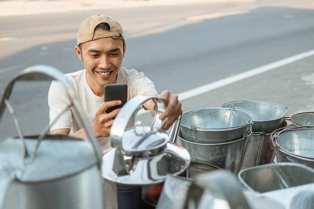 家電店でやかんの写真を撮るときに電話カメラを使用してアジアの男性売り手スクワットのクローズアップ
