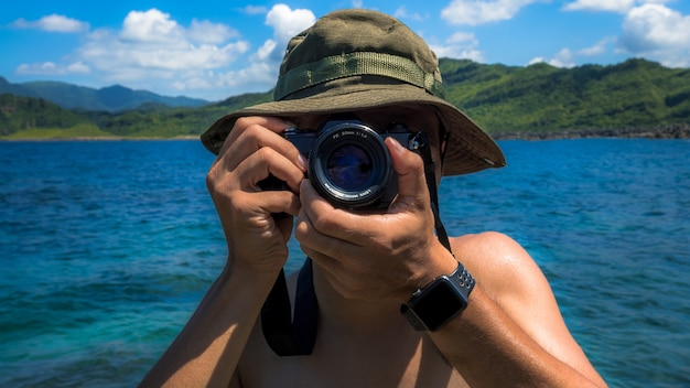 Крупным планом азиатского фотографа, делающего снимки с аналоговой камерой, стоя на красивом пляже с фоном гор и голубым небом на тайване