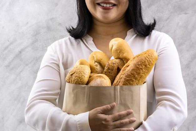 使い捨て紙袋に様々なパンを保持しているアジアの笑顔の女性主婦のクローズアップ。パン屋さんの食べ物や飲み物の食料品と家庭生活のライフスタイルのコンセプトを配信します。
