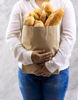Закройте вверх азиатской домохозяйки женщины улыбки держа хлеб разнообразия в одноразовом бумажном пакете на серой винтажной предпосылке просторной квартиры. хлебобулочные продукты и напитки, бакалея и концепция домашнего образа жизни для доставки.