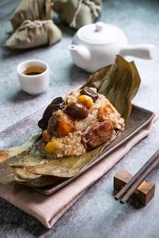 ドラゴンボート(ドゥアンウー)フェスティバルでアジアのおいしい自家製食品のクローズアップ、餃子やzongziが黒の表面にお茶と皿の上の乾燥した笹の葉で包んだ