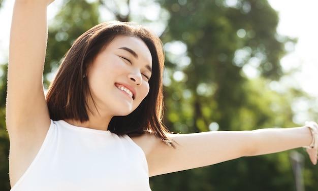 손을 위로 뻗고 웃고, 공원에서 산책하고, 평온하고 행복하게 보이는 아시아 여자의 근접