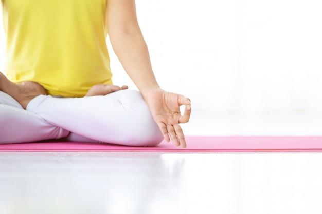 Крупный план тренировки азиатских женщин, практикующих обучение йоге, одетых в желтое платье и практикующих медитацию, оздоровительный образ жизни и фитнес-концепцию в тренажерном зале, copy space