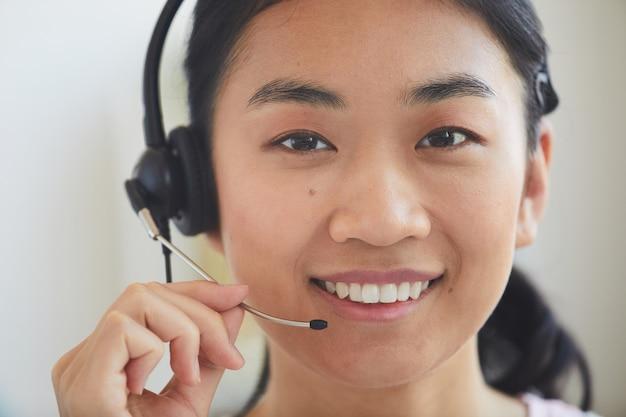 笑顔のヘッドフォンでアジアの若いオペレーターのクローズアップ