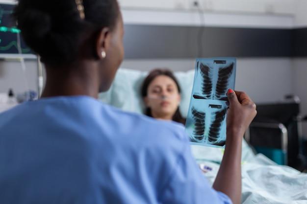 아픈 여성에게 폐 방사선 사진을 설명하는 검은 피부를 가진 조수 클로즈업