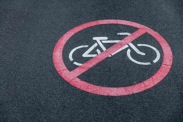 自転車に乗ることを禁止するための赤い記号が印刷されたアスファルト道路のクローズアップ。警告を示す道路標識。自転車道はありません。