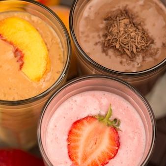 Крупный план ассортимента молочных коктейлей с шоколадом и фруктами