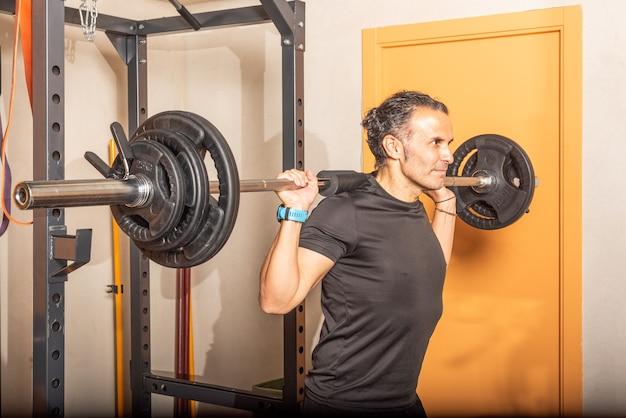 체육관에서 바와 함께 쪼그리고 앉는 운동 선수 남자의 닫습니다. 체육관에서 운동의 개념입니다.