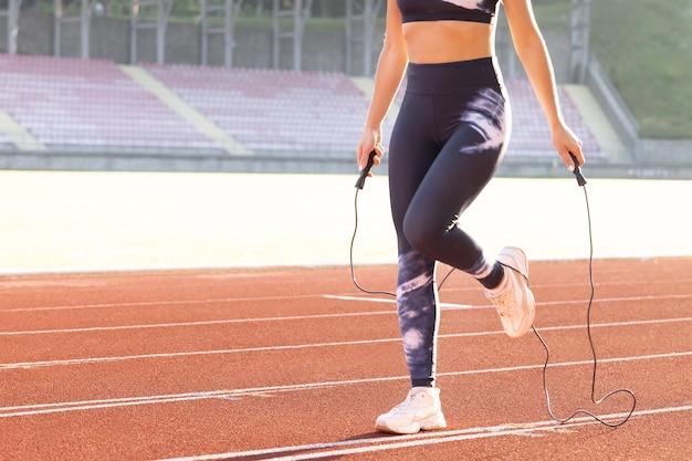 Закройте вверх спортивной кавказской женщины, прыгающей через скакалку как часть ее спортивной женщины тренировки фитнеса