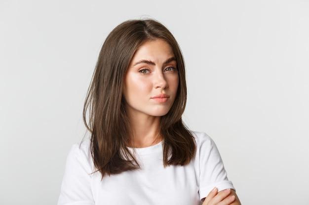 Крупный план привлекательной девушки брюнетки, выглядящей скептически и недовольной.