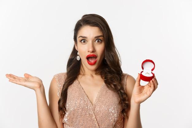 Крупный план привлекательной брюнетки с красными губами, одетой в платье, получая обручальное кольцо и смотрящей с сюрпризом, стоя на белом фоне.