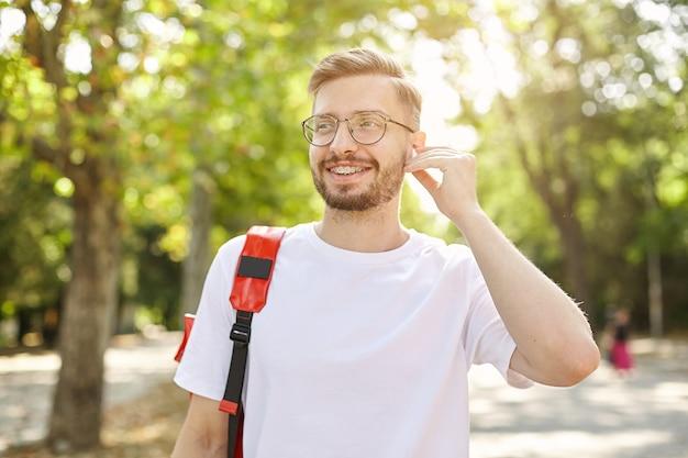 魅力的な陽気な男性のクローズアップ、目をそらし、広く笑って、眼鏡とヘッドフォンを着用し、明るく暖かい日に公園を歩いています