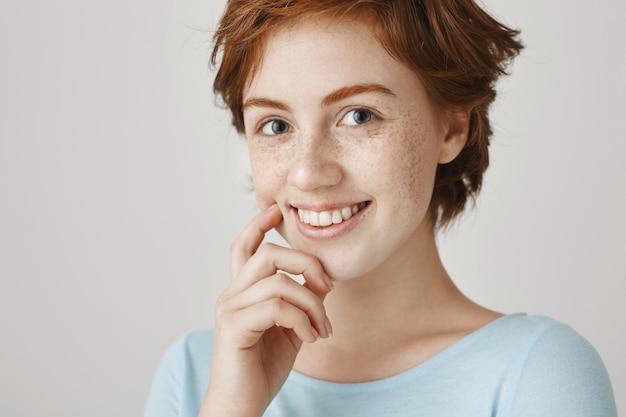 笑顔で愛らしい魅力的なコケティッシュな赤毛の女の子のクローズアップ